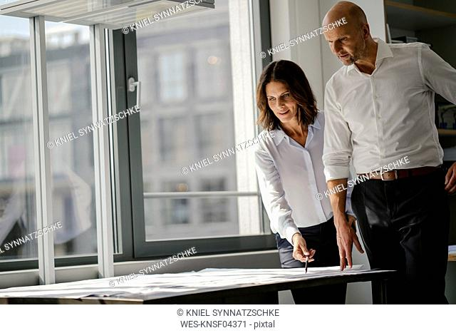 Two architects working in office, discussing blueprints