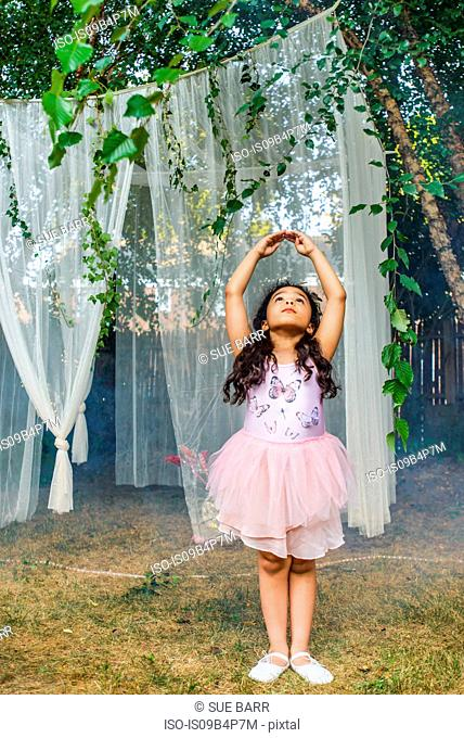 Portrait of young girl, dressed as fairy, dancing outdoors