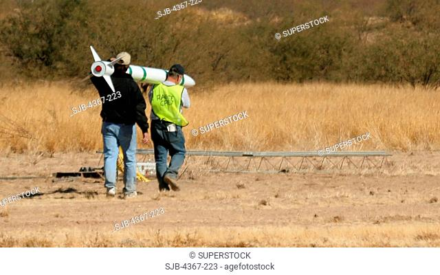 Larry Foster in dark jacket carries a long green and white rocket out to a launch gantry at a launch event sponsored by the Southern Arizona Rocketry...