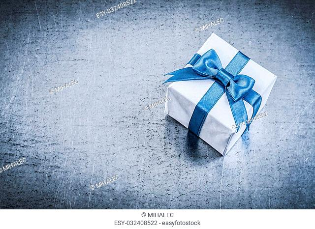 Giftbox with tied bow on metallic background holidays concept