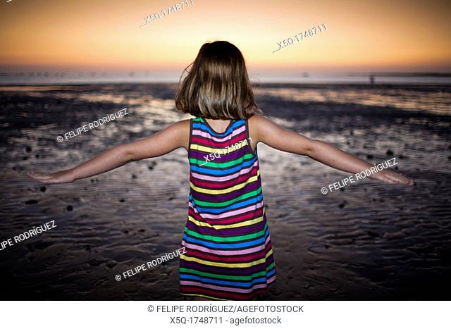 Little girl on the beach at dusk, Spain