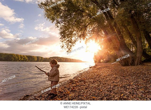 Morning scene at River Rhine in Bonn, Germany. 2 year old playing with stick at river
