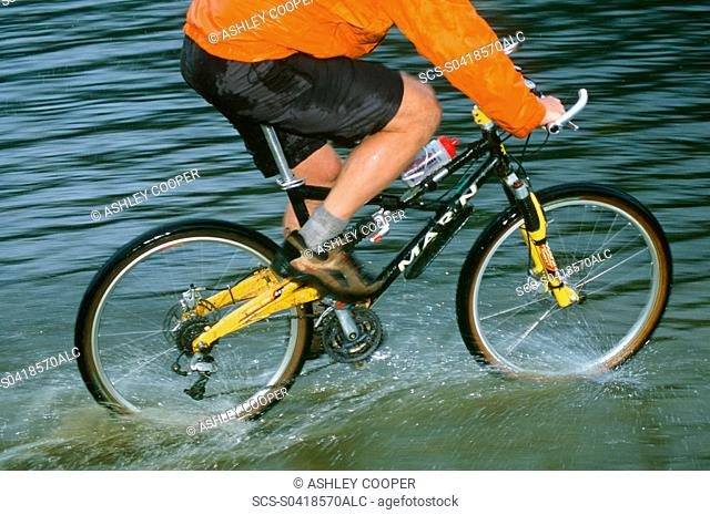 A mountain biker riding through Rydal Water in the Lake District UK