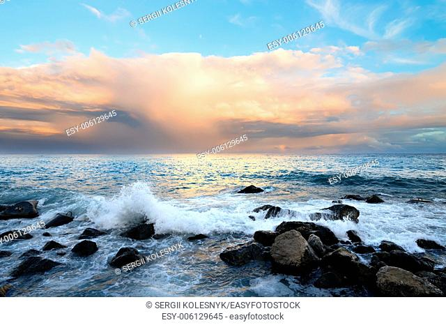 Rocky coast and sea waves at sunset