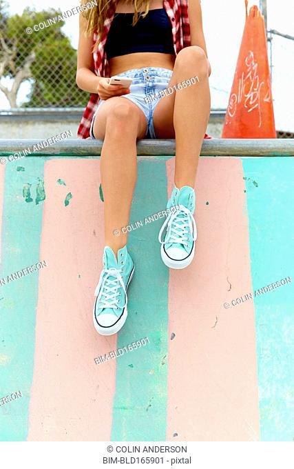 Woman sitting on ramp at skate park