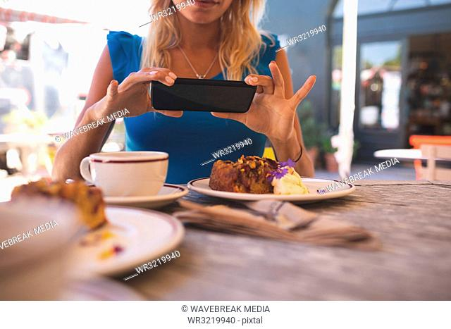 Woman taking picture from mobile phone in outdoor cafe
