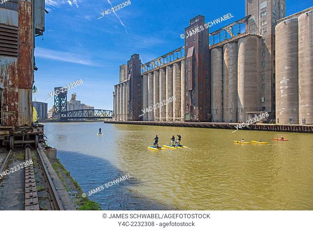 Paddleboarding and kayaking in the Buffalo River along historic abandoned grain elevators on the waterfront in Buffalo, New York