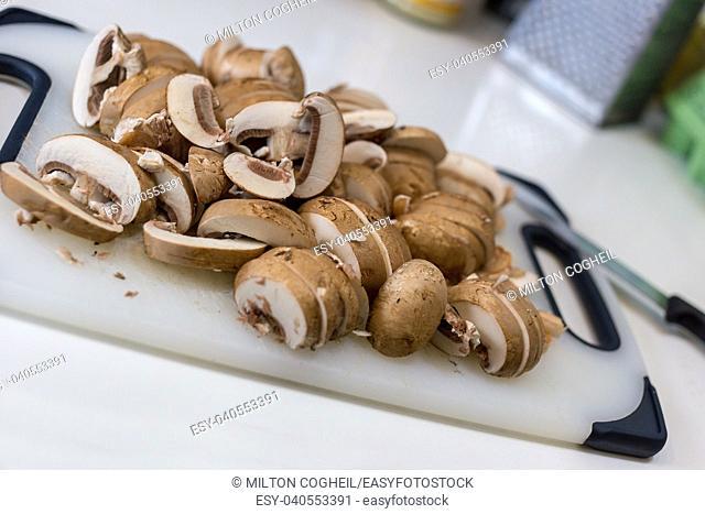 A pile of sliced chestnut mushrroms (Agaricus bisporus) on a white chopping board
