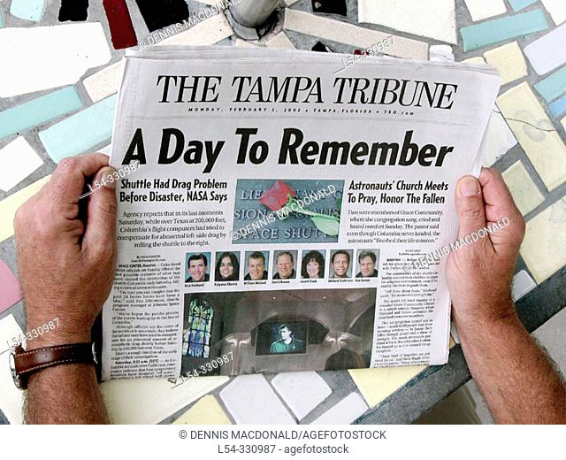 Adult reads newspaper about space ship Columbia tragedy