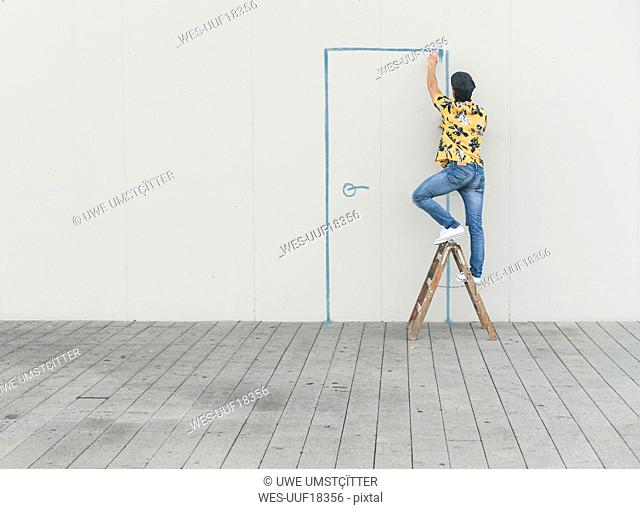 Digital composite of young man drawing a door at a wall