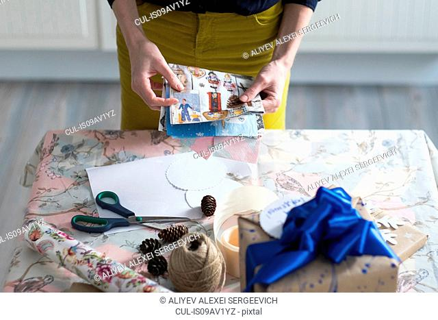 High angle view of mid adult woman wrapping gift at table