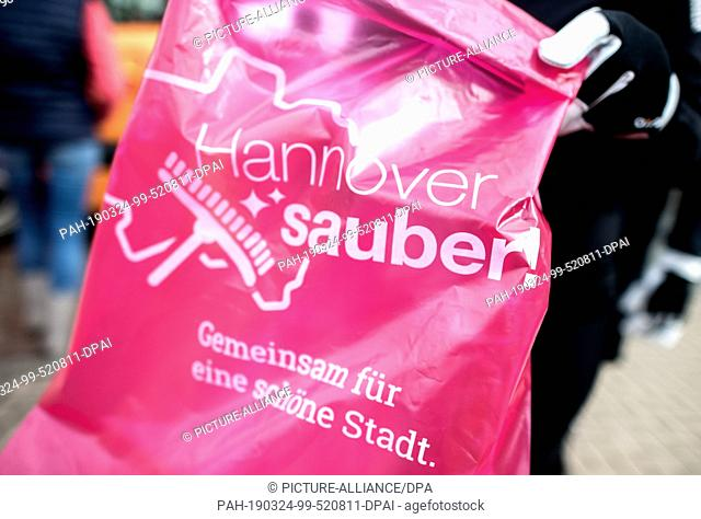 """24 March 2019, Lower Saxony, Hannover: A jogger near the Noltemeyer bridge in the Bothfeld district holds a garbage bag with the inscription """"""""Hannover sauber"""