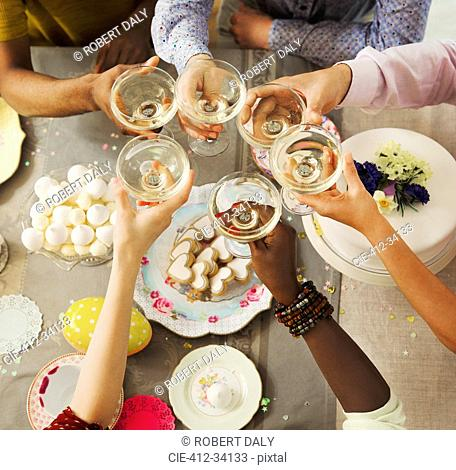 Overhead view friends toasting champagne glasses over Easter desserts