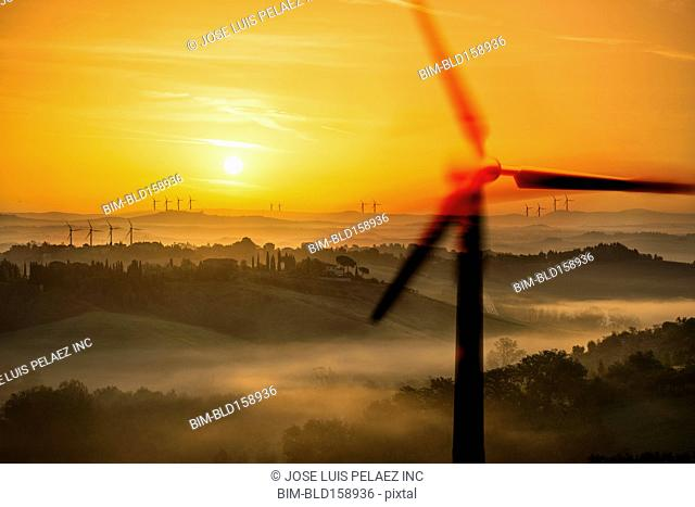 Blurred view of wind turbines over rural landscape