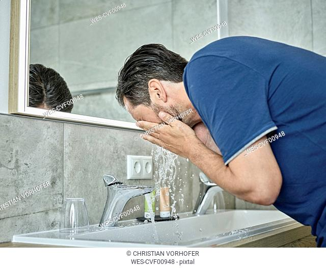 Man washing his face in bathroom