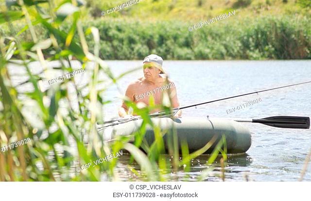 Elderly fisherman fishing off a dinghy near reeds