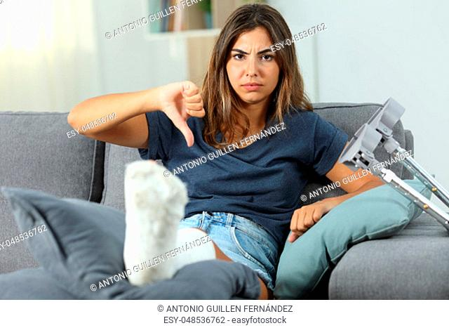 Angry disabled woman gesturing thumbs down sitting on a couch in the living room at home