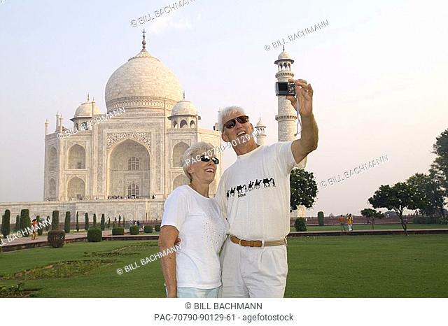 India, Agra, tourist couple taking photo of themselves in front of the Taj Mahal
