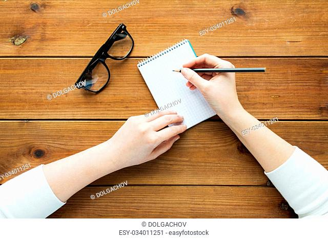 education, business and people concept - close up of woman or student writing to notepad with pencil and eyeglasses on wooden table