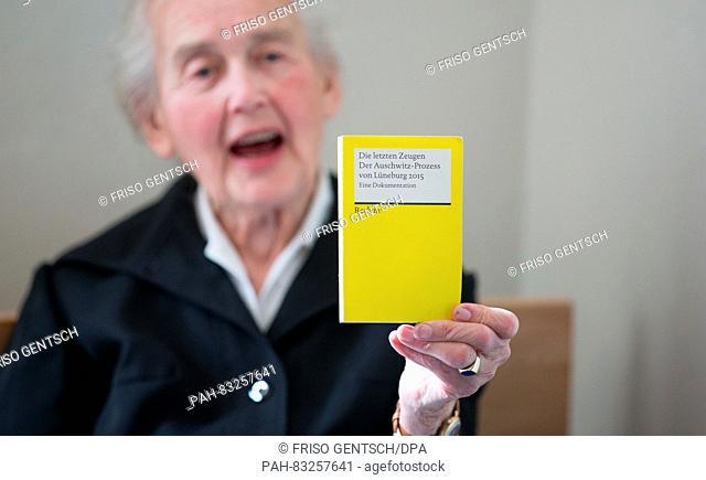 Defendant Ursula Haverbeck holding up a book called 'Die letzten Zeugen. Der Auschwitz-Prozess von Lueneburg 2015' (lit. 'The last witnesses