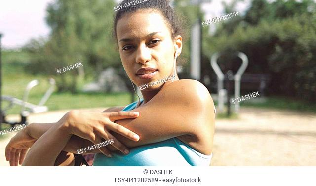 Portrait of young ethnic girl with headphones warming up hands and looking confidently at camera on background of summer park