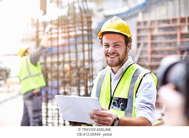 Portrait confident construction worker with digital tablet at construction site