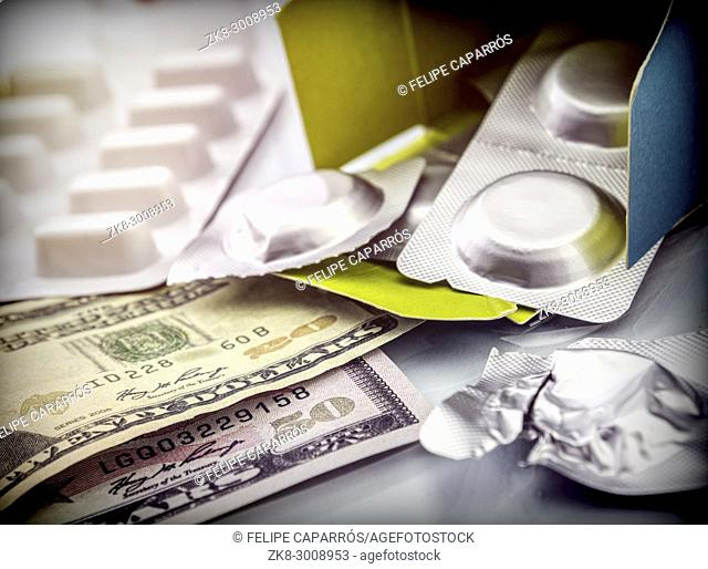 Some medicines next to a block of tickets of dollar, conceptual image
