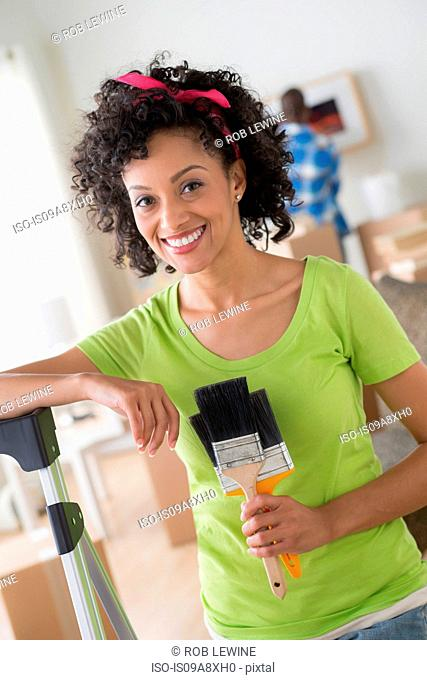 Mid adult woman holding paintbrushes