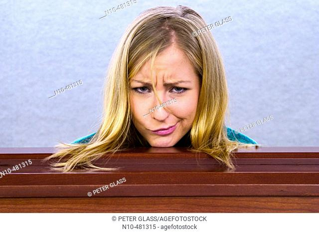 Young blond woman's head resting on a ledge in an office building