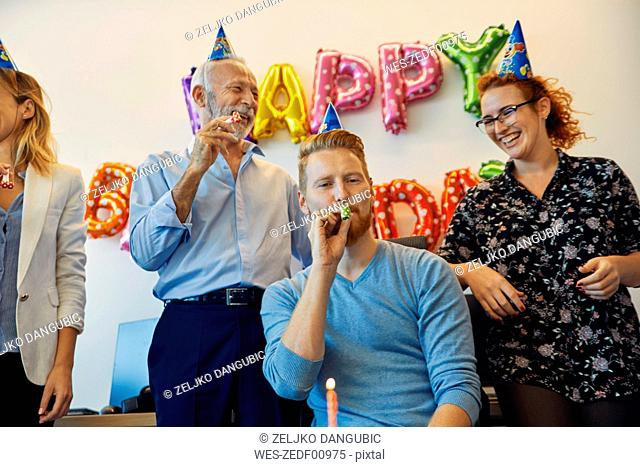 Colleagues having a birthday celebration in office with party blower and party hats