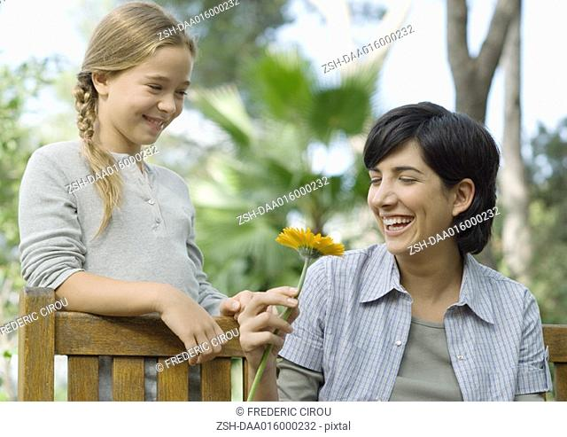 Mother and daughter, mother holding flower