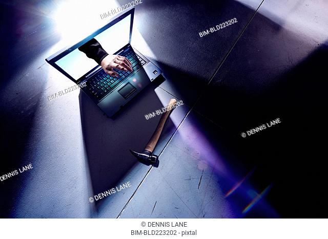 Hand of hacker reaching from screen of laptop and typing