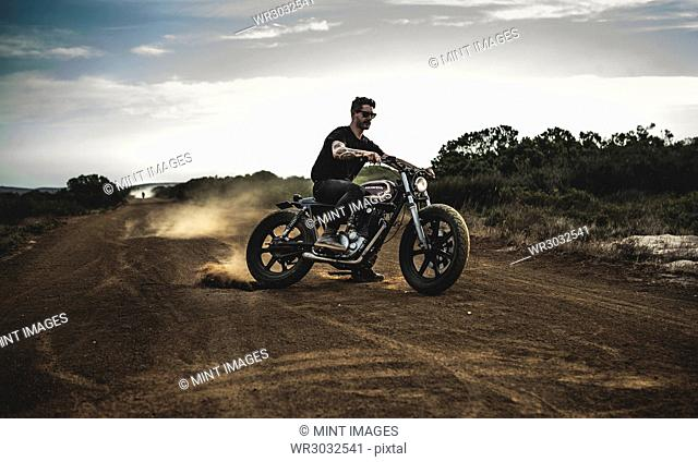 Man wearing sunglasses riding cafe racer motorcycle on a dusty dirt road, sliding sideways