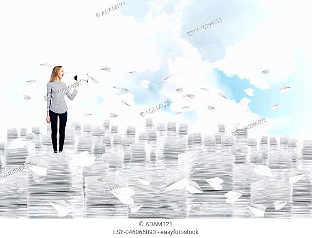 Woman in casual clothing standing on pile of documents among flying paper planes with speaker in hand with cloudly skyscape on background. Mixed media