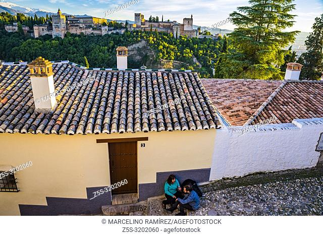 Narrow street in the Sacromonte - Albaicin, in the background, sunset over the Alhambra. Granada, Andalucia, Spain, Europe