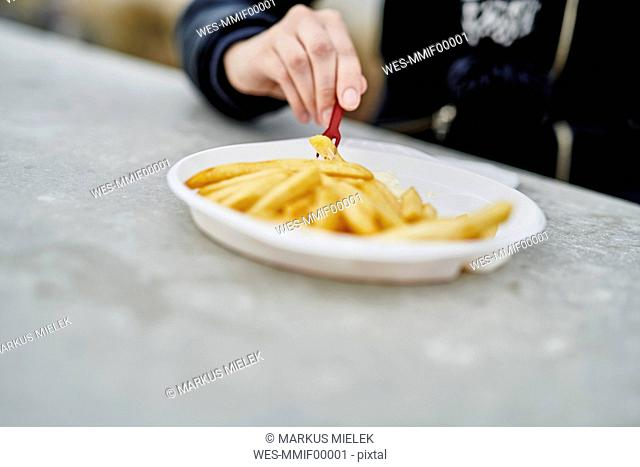 Woman eating French Fries, close-up