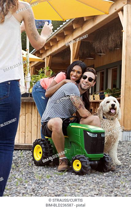 Woman photographing couple and dog with cell phone