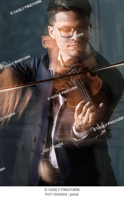 Blurred motion of violinist playing violin against wall