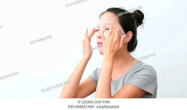 Woman apply paper mask and massaging on face