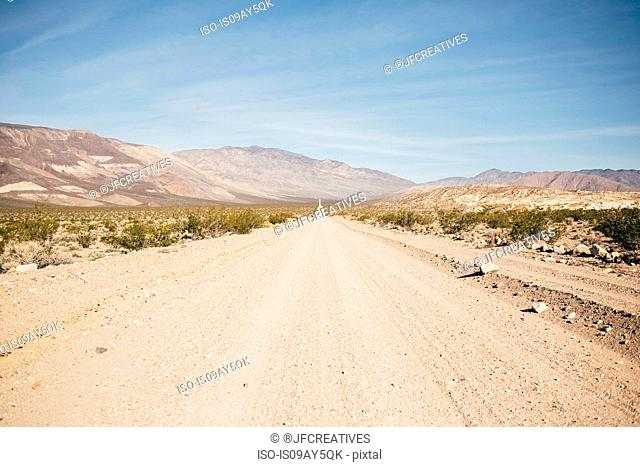 Straight dirt track road in desert landscape, Olancha, California, USA