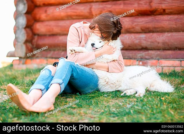 young stylish hipster woman girl playing white kid-skin dog in country side, village wood house, cool outfit, romantic mood, having fun, ripped jeans