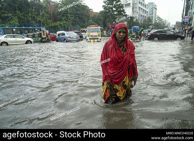 A woman walks through rain water on the streets during the monsoon rain. Couple of hours of rain create waterlogging on the streets as the sewerage and drains...