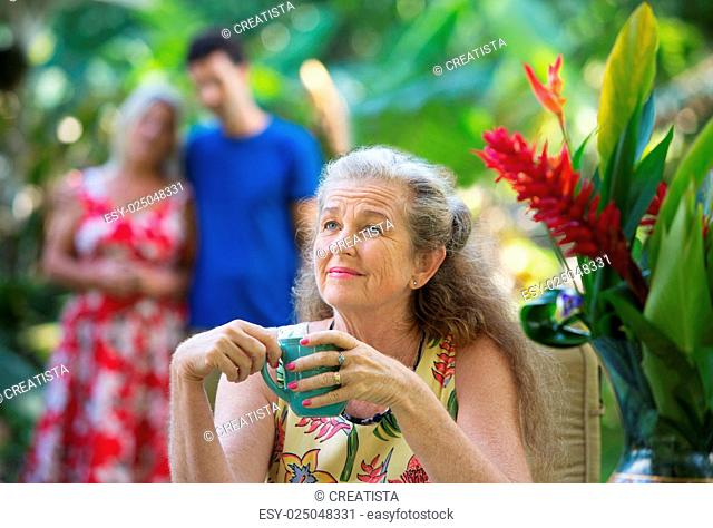 Forgetful older mother with cup near couple