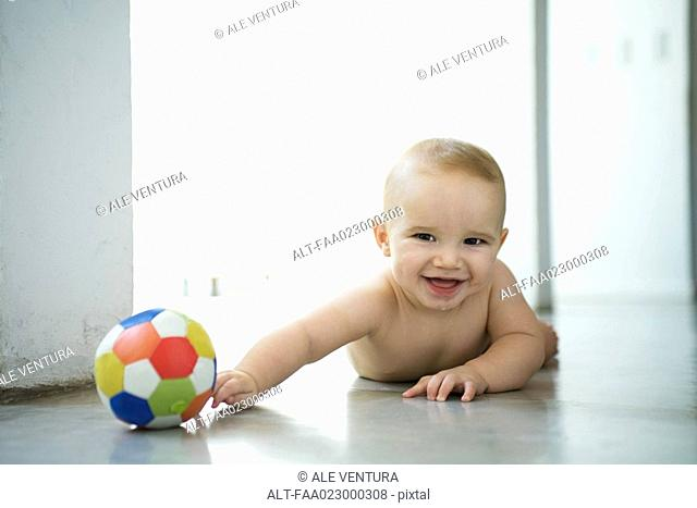 Baby lying on floor with ball, laughing and looking at camera