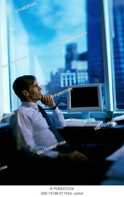 Side profile of a businessman sitting with his hand on his chin