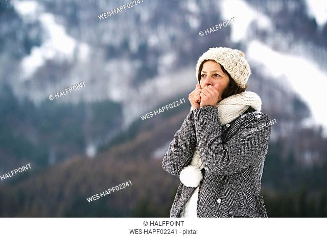 Portrait of senior woman warming her hands in winter