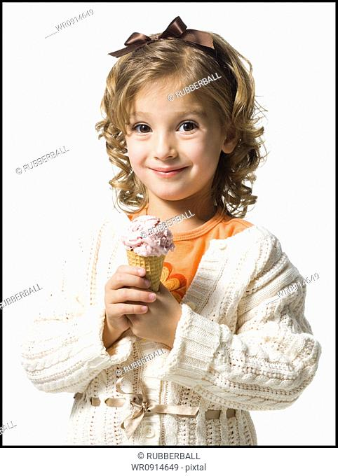 Smiling young girl in white sweater eating ice cream cone