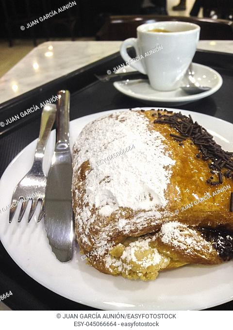 Having pain au chocolat or napolitana at Coffee Shop. Cake with plate, tray, coffee cup and cutlery. Selective focus