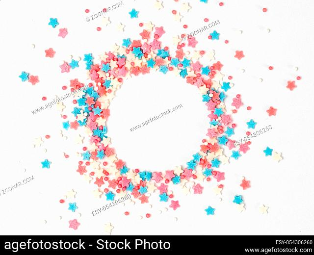 Festive border frame of colorful pastel sprinkles on white background with copy space in center. Sugar sprinkle dots and stars in round shape