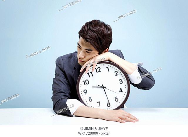 A business man hugging a clock